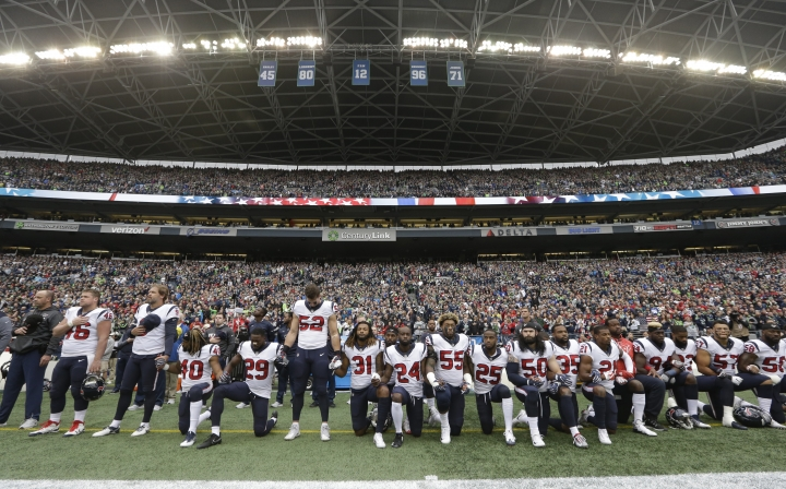 "FILE - In this Oct. 29, 2017, file photo, Houston Texans players kneel and stand during the singing of the national anthem before an NFL football game against the Seattle Seahawks, in Seattle. NFL owners have approved a new policy aimed at addressing the firestorm over national anthem protests, permitting players to stay in the locker room during the ""The Star-Spangled Banner"" but requiring them to stand if they come to the field. The decision was announced Wednesday, May 23, 2018, by NFL Commissioner Roger Goodell during the league's spring meeting in Atlanta. (AP Photo/Elaine Thompson, File)"
