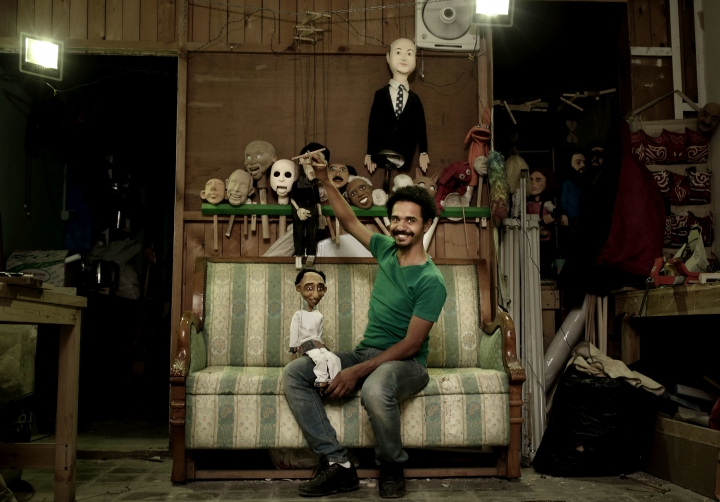 In this April 24, 2018 photo, Egyptian artist Mohamed Fawzi Bakkar poses for a photograph with his favorite puppets at his workshop, in Cairo, Egypt. Bakkar designs and builds marionettes from scratch, hoping to revive a traditional art. The 32-year-old spends hours or even days designing puppets inspired by Egyptian life -- farmers, street vendors, butchers and the occasional celebrity. (AP Photo/Nariman El-Mofty)