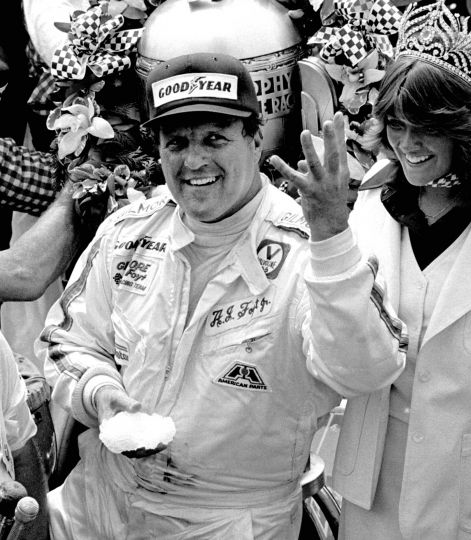 FILE - In this May 29, 1977, file photo, driver A.J. Foyt holds up four fingers in Victory Lane after winning his fourth Indianapolis 500 auto race at Indianapolis Motor Speedway in Indianapolis. Foyt won the Indy 500 auto race in 1961, 1964, 1967 and 1977. He's been coming to Indianapolis every May since 1958 and every year, crowds gather around the first garage stall in Gasoline Alley waiting to have an old photograph signed by their racing hero or merely to catch a glimpse of the former racing star. (AP Photo/File)