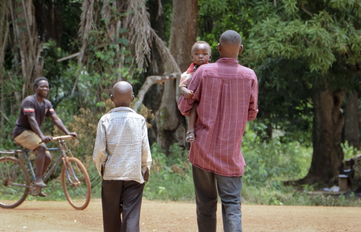 In this photo taken Tuesday, March 13, 2018, James Seferino, 11, left, walks with his father Andrea Seferino, right, both of whom are HIV-positive, while his father carries his baby son who has not got the virus after receiving treatment for HIV at a Doctors Without Borders clinic outside the town of Yambio, in South Sudan. South Sudan's five-year civil war is quietly creating another kind of victim - those prevented from accessing life-saving antiretroviral medicine, and experts say the number of affected people could be in the hundreds of thousands. (AP Photo/Sam Mednick)