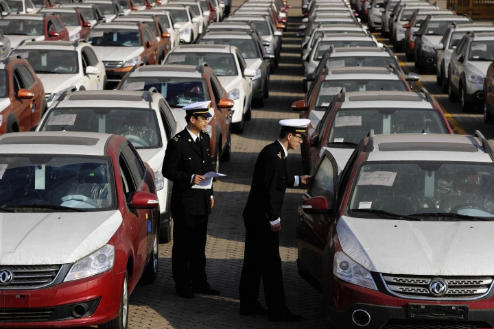"""In this Jan. 14, 2015 photo, Chinese customs officials inspect cars being loaded for export at a port in Qingdao in eastern China's Shandong province. China said Thursday, May 24, 2018, that it will """"firmly defend"""" its rights and interests against what it calls the Trump administration's abuse of national security provisions in trade. The Commerce Ministry's response came after the Trump administration launched an investigation into whether tariffs are needed on automobile imports on national security grounds. (Chinatopix via AP)"""