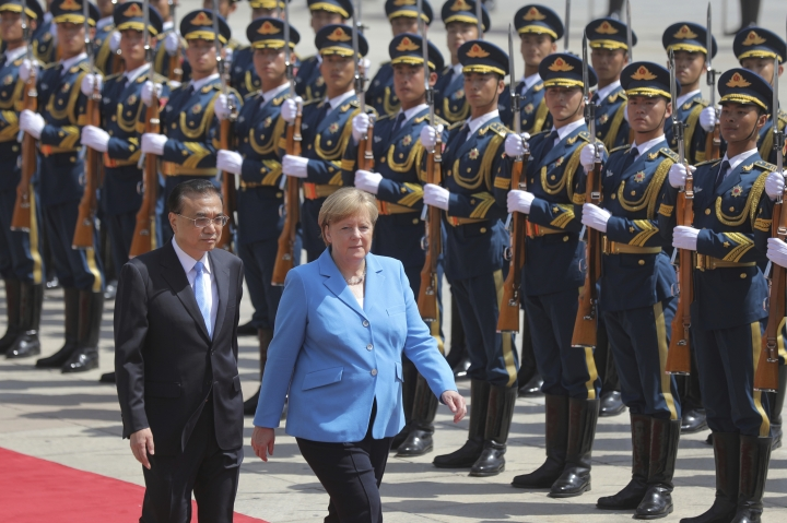 German Chancellor Angela Merkel, right, and Chinese Premier Li Keqiang walk past the People's Liberation Army honor guards during a welcoming ceremony at the Great Hall of the People in Beijing, Thursday, May 24, 2018. The German Chancellor is on a state visit to China from May 24-25. (Wu Hong/Pool Photo via AP)