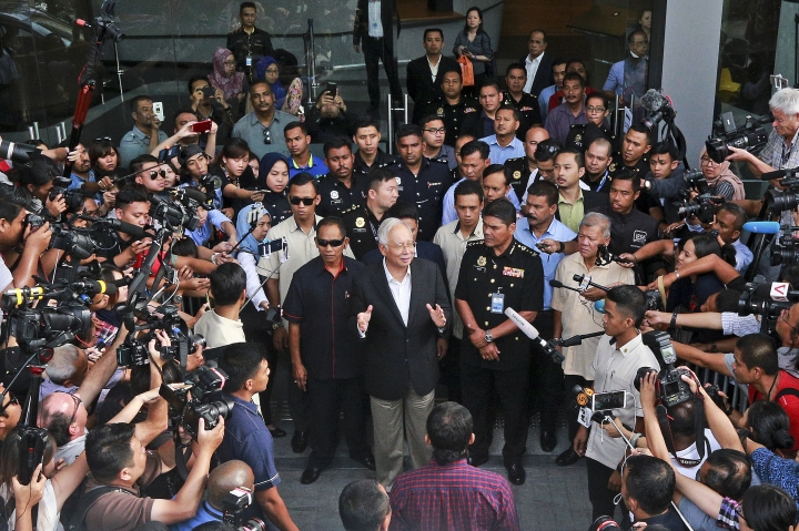 Former Malaysian Prime Minister Najib Razak, center, speaks to media as he leaves the Malaysian Anti-Corruption Commission (MACC) Office in Putrajaya, Malaysia, Thursday, May 24, 2018. Former Malaysian Prime Minister Najib Razak was being questioned again Thursday by anti-graft investigators looking into alleged theft and money laundering at a state investment fund he had founded that accumulated billions in debt. (AP Photo/Sadiq Asyraf)