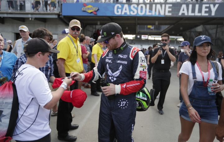 Conor Daly signs an autograph for a fan after he qualified for the IndyCar Indianapolis 500 auto race at Indianapolis Motor Speedway in Indianapolis, Saturday, May 19, 2018. (AP Photo/Michael Conroy)