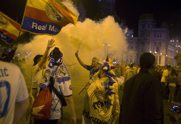 Real Madrid fans celebrate after lighting a flare in downtown Madrid, Spain, Saturday, May 26, 2018. Real Madrid defeated Liverpool in Kiev, Ukraine, to win the Champions League soccer match final. (AP Photo/Paul White)