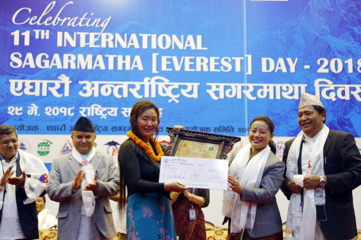 Nepalese woman climber Lhakpa Sherpa, center left, is honored with an honorary certificate in Kathmandu, Nepal, Tuesday, May 29, 2018. Nepal has honored several Sherpa guides for their own Everest successes on the anniversary of the first conquest of the world's highest peak. (AP Photo/Niranjan Shrestha)