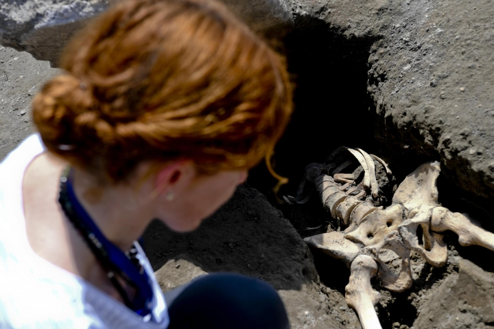 Anthropologist Valeria Amoretti looks at a skeleton of a victim of the eruption of Mt. Vesuvius in A.D. 79, which destroyed the ancient town of Pompeii, at Pompeii' archeological site, near Naples, on Tuesday, May 29, 2018. The skeleton was found during recent excavations and is believed to be of a 35-year-old man with a limp who was hit by a pyroclastic cloud during the eruption. (Ciro Fusco/ANSA via AP)
