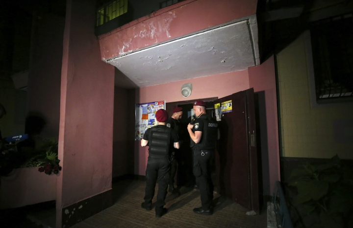 Police guard the front door of the multi-storey building where Russian opposition journalist Arkady Babchenko lived, in Kiev, Ukraine, Tuesday, May 29, 2018. Police in the capital of Ukraine say a Russian journalist has been shot and killed at his Kiev apartment. Ukrainian police said Arkady Babchenko's wife found him bleeding at the apartment on Tuesday and called an ambulance, but Babchenko died on the way to a hospital. (AP Photo/Sergiy Nuzhnenko)