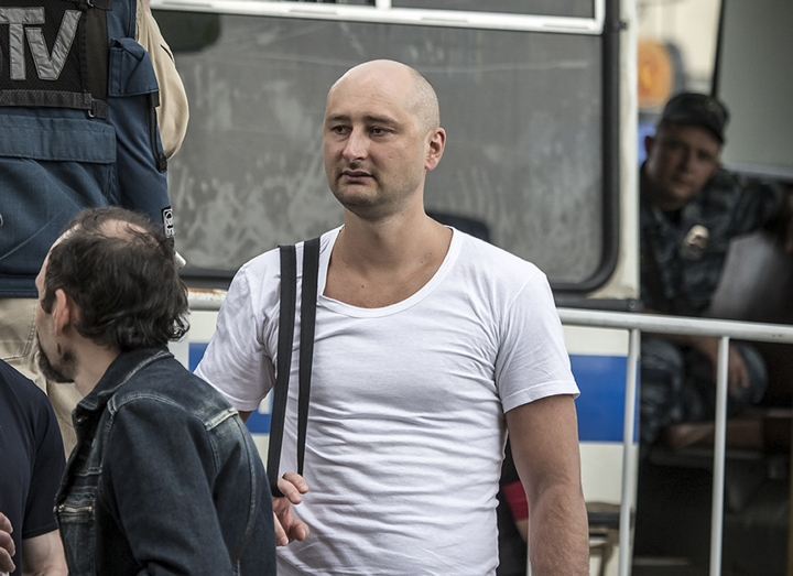 In this photo taken on Friday, May 31, 2013, Arkady Babchenko, 41, who had been scathingly critical of the Kremlin in recent years, stands at a police bus during an opposition rally in Moscow, Russia. Police in the capital of Ukraine say a Russian journalist has been shot and killed at his Kiev apartment. Ukrainian police said Arkady Babchenko's wife found him bleeding at the apartment on Tuesday, May 29, 2018 and called an ambulance, but Babchenko died on the way to a hospital. (AP Photo/Alexander Baroshin)