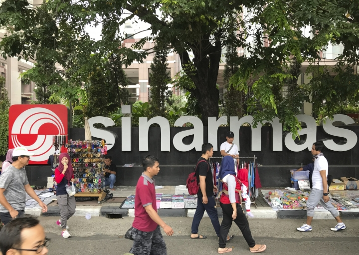 FILE - In this Oct. 1, 2017, file photo, people walks past Sinarmas Land Plaza during a car-free day at the main business district in Jakarta, Indonesia. Forest Stewardship Council, the main global group for certifying sustainable wood, has sent a come-clean ultimatum to Sinarmas, one of the world's largest paper companies following evidence it continues to cut down tropical forests and hide activities behind corporate proxies. (AP Photo/Dita Alangkara, File)