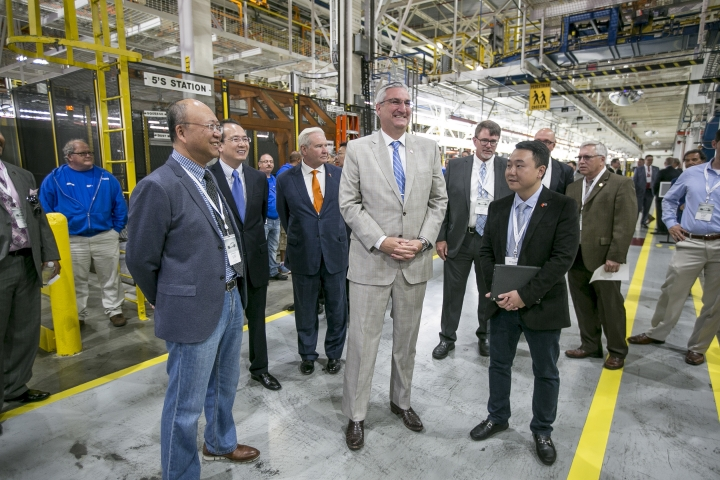 SF Motors CEO John Zhang,, and Indiana Gov. Eric Holcomb, center, tour the SF Motors assembly plant Wednesday, May 30, 2018, in Mishawaka, Ind. SF Motors, an electric vehicle startup, announced Wednesday that it is retooling an Indiana factory and hopes to conduct trial runs for two new lines of vehicles by the end of the year. (Santiago Flores/South Bend Tribune via AP)