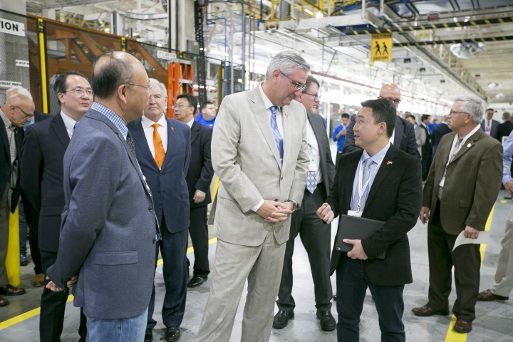 SF Motors CEO John Zhang right, and Indiana Gov. Eric Holcomb, center, speak as they tour the SF Motors assembly plant Wednesday, May 30, 2018, in Mishawaka, Ind. SF Motors, an electric vehicle startup, announced Wednesday that it is retooling the Indiana factory and hopes to conduct trial runs for two new lines of vehicles by the end of the year. (Santiago Flores/South Bend Tribune via AP)