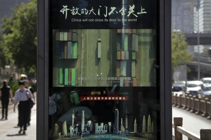 In this Wednesday, May 30, 2018, photo, people walk by an electronic display panel advertising a video footage of China trade business on a street in Beijing. China has criticized proposed U.S. investment controls as a violation of global trade rules and says it reserves the right to retaliate if they take effect. (AP Photo/Andy Wong)