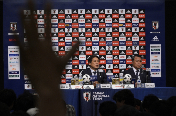 A journalist rises his hand to ask questions to Japanese men's national soccer coach Akira Nishino, left, during a press conference to announce Japanese squad members for the World Cup Russia in Tokyo Thursday, May 31, 2018. Nishino named his 23-man World Cup squad, relying heavily on veteran players with previous experience in the tournament. At right is Japan Football Association President Kozo Tashima. (AP Photo/Eugene Hoshiko)