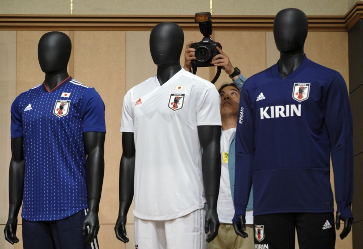 A photographer takes a picture near mannequins with Japan's national team official wears prior to a press conference to announce Japanese squad members for the World Cup Russia in Tokyo Thursday, May 31, 2018. Japan coach Akira Nishino named his 23-man World Cup squad, relying heavily on veteran players with previous experience in the tournament. (AP Photo/Eugene Hoshiko)
