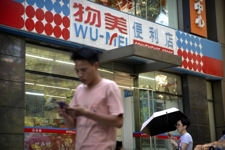 People walk past a Wumei convenience store, part of the Wumart Stores retail company, in Beijing, Thursday, May 31, 2018. China's supreme court has thrown out the fraud conviction of a retail tycoon in an unusual gesture of official leniency toward entrepreneurs amid a string of high-profile detentions and prosecutions that has rattled the Chinese business world. (AP Photo/Mark Schiefelbein)