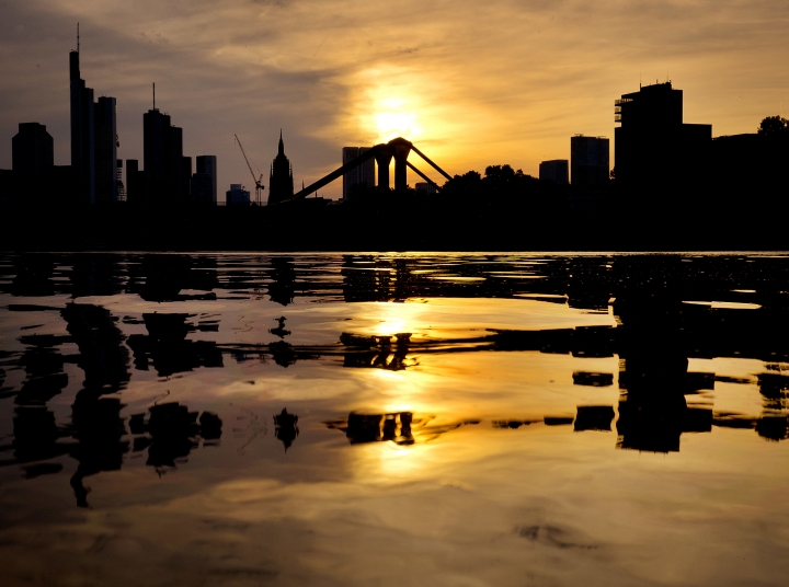 The buildings of the banking district are reflected in the river Main as the sun sets in Frankfurt, Germany, Monday evening, May 28, 2018. (AP Photo/Michael Probst)