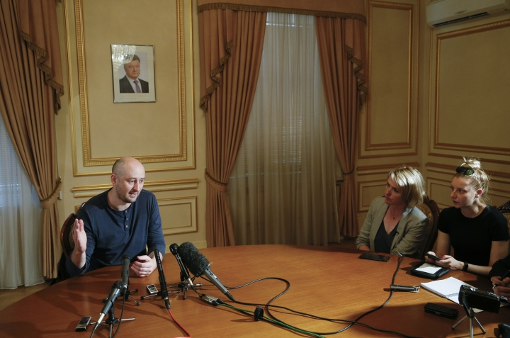 Russian journalist Arkady Babchenko, left, speaks during an interview with foreign media, with the portrait of Ukrainian President Petro Poroshenko, center in the background, in Kiev, Ukraine, Thursday, May 31, 2018. Arkady Babchenko detailed the deception to reporters Thursday for the first time since Ukrainian authorities revealed they had staged his death to foil an alleged plot on his life by Moscow's security services. (Valentyn Ogirenko/Pool Photo via AP)