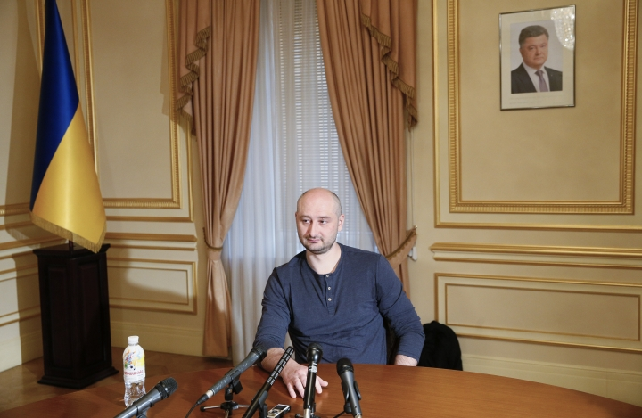 Russian journalist Arkady Babchenko speaks during an interview with foreign media, with the portrait of Ukrainian President Petro Poroshenko, right in the background, in Kiev, Ukraine, Thursday, May 31, 2018. Arkady Babchenko detailed the deception to reporters Thursday for the first time since Ukrainian authorities revealed they had staged his death to foil an alleged plot on his life by Moscow's security services. (Valentyn Ogirenko/Pool Photo via AP)