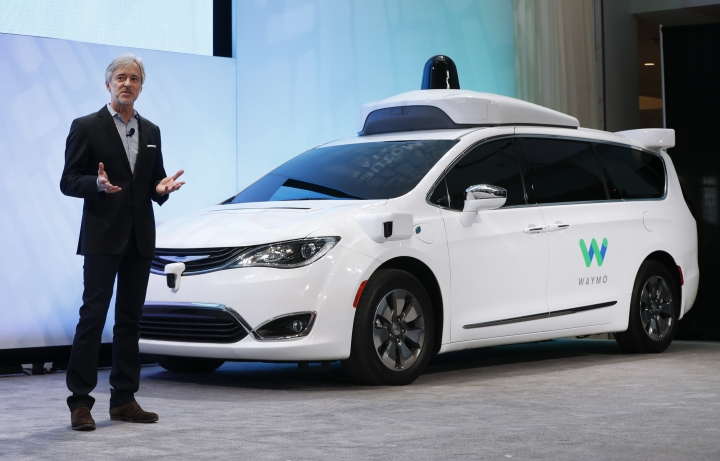 FILE - In this Sunday, Jan. 8, 2017, file photo, John Krafcik, CEO of Waymo, the autonomous vehicle company created by Google's parent company, Alphabet, introduces a Chrysler Pacifica hybrid outfitted with Waymo's own suite of sensors and radar, at the North American International Auto Show in Detroit. A self-driving car service that Google spinoff Waymo plans to launch later this year in Arizona will include up to 62,000 Chrysler Pacifica Hybrid minivans under a deal announced Thursday, May 31, 2018. (AP Photo/Paul Sancya, File)