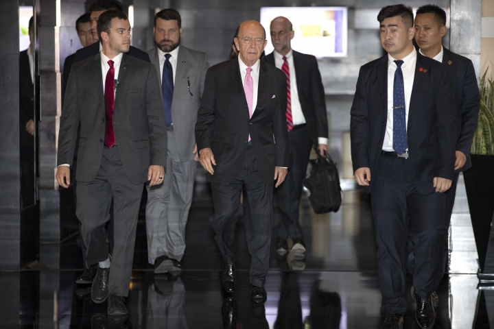 U.S. Commerce Secretary Wilbur Ross, center, leaves his hotel in Beijing, Saturday, June 2, 2018. U.S. Commerce Secretary Ross has arrived in Beijing for talks on China's promise to buy more American goods after Washington revived tensions by renewing its threat of tariff hikes on Chinese high-tech exports. (AP Photo/Mark Schiefelbein)