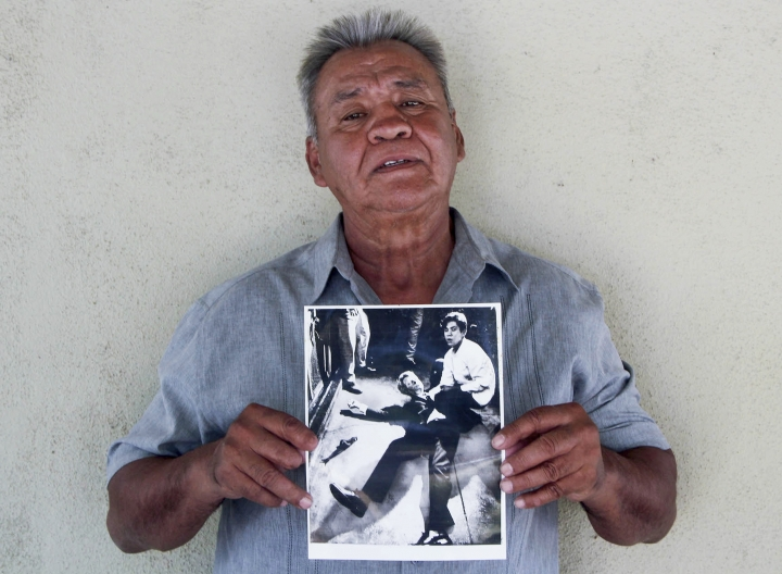 """In this undated photo provided by StoryCorps, Juan Romero, 67, holds a photo of himself and the dying Sen. Robert F. Kennedy at the Ambassador Hotel in Los Angeles, taken by the Los Angeles Times' Boris Yaro on June 5, 1968, at his home in Modesto, Calif. Associated Press Hollywood reporter Bob Thomas was on a one-night political assignment covering Sen. Robert F. Kennedy's victory celebration in the California presidential primary at the Ambassador Hotel when mayhem unfolded before his eyes. He heard pops of gunfire, then screams, and quickly rushed into the kitchen to see the dying Kennedy on the floor, blood oozing from his head. He found a phone and called the AP desk. """"I've got a flash. Kennedy shot."""" Sirhan Sirhan was later convicted of Kennedy's murder. (Jud Esty-Kendall/StoryCorps via AP)"""