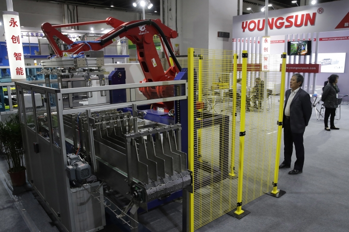 In this April 12, 2018, photo, a visitor watches a Chinese company displaying a Chinese-made industrial robot demonstration on processing soybean at the International soybean exhibition in Shanghai. China says it will narrow its trade surplus with the United States but rejects pressure to change technology development tactics seen as a path to prosperity and its rightful place as a global leader. Beijing highlighted the sensitivity of the issue with its threat to scrap deals aimed at settling a sprawling trade dispute with Washington if President Donald Trump's threatened tariff hike on $50 billion of Chinese technology goes ahead. (AP Photo/Andy Wong)