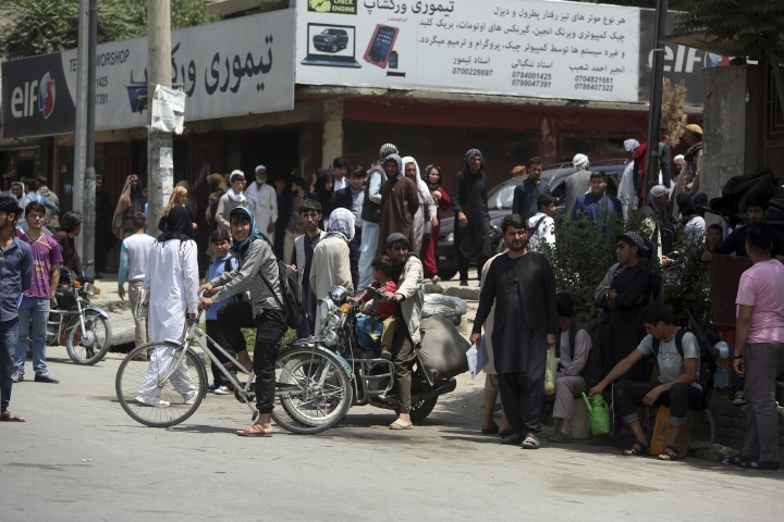 Afghan bystanders watch the aftermath of a deadly suicide attack in Kabul, Afghanistan, Monday, June 4, 2018. A suicide bombing targeted a gathering of Afghanistan's top clerics on Monday in Kabul, killing at least seven people and wounding nine. (AP Photo/Rahmat Gul)