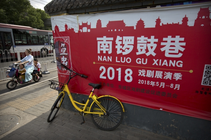"A woman and children ride a motorbike past an advertisement for the Nanluoguxiang Performing Arts Festival in Beijing, Tuesday, June 5, 2018. Renowned Australian playwright David Williamson said on Tuesday that he was disappointed Beijing censors had canceled a production of his play ""The Removalists"" officially because of bad language and violence. (AP Photo/Mark Schiefelbein)"