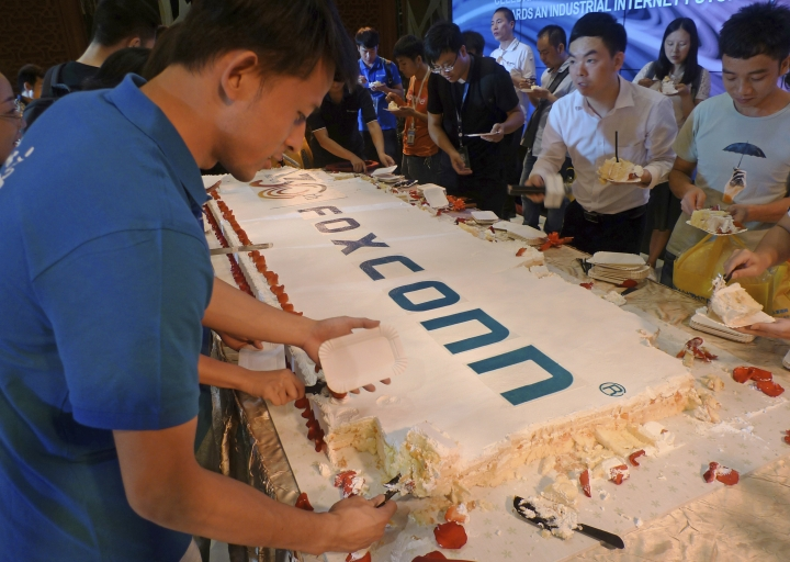 Workers cut a giant cake to celebrate Taiwan-based contract manufacturing giant Foxconn's 30th anniversary of its first investment in Shenzhen, south China's Guangdong province Wednesday, June 6, 2018. The head of Taiwan's Foxconn, which assembles Apple iPhones and other tech products, says Washington's dispute with China is over technology rather than trade. (AP Photo/Kelvin Chan)