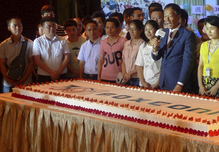 Foxconn Chairman Terry Gou, second from right, prepare to cut a giant cake at an event to celebrate Taiwan-based contract manufacturing giant Foxconn's 30th anniversary of its first investment in Shenzhen, south China's Guangdong province Wednesday, June 6, 2018. The head of Taiwan's Foxconn, which assembles Apple iPhones and other tech products, says Washington's dispute with China is over technology rather than trade. (AP Photo/Kelvin Chan)