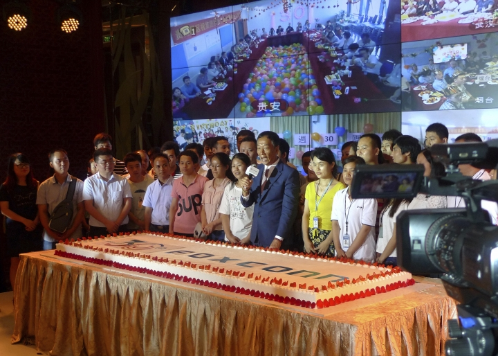 Foxconn Chairman Terry Gou, center, prepares to cut a giant cake at an event to celebrate Taiwan-based contract manufacturing giant Foxconn's 30th anniversary of its first investment in Shenzhen, south China's Guangdong province Wednesday, June 6, 2018. The head of Taiwan's Foxconn, which assembles Apple iPhones and other tech products, says Washington's dispute with China is over technology rather than trade. (AP Photo/Kelvin Chan)
