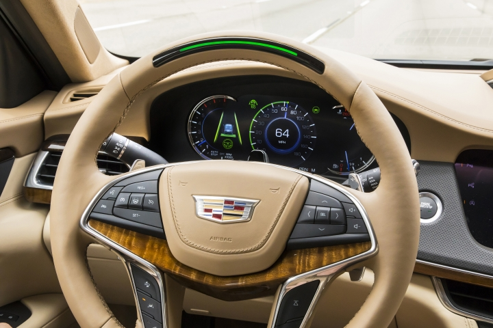 In this undated photo provided by General Motors a steering wheel light bar and cluster icons indicates an active status of Super Cruise in a Cadillac with the green light bar. General Motors is going to expand a hands-free driver-assist system to all Cadillac vehicles starting in 2020, with plans to roll it out to more brands in the future. (Wes Allison/Courtesy of General Motors via AP)