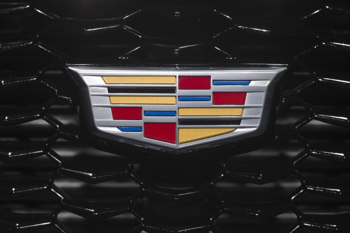 FILE- In this March 27, 2018, file photo the Cadillac emblem is shown on the from grill of its XT4 at the New York Auto Show. General Motors is going to expand a hands-free driver-assist system to all Cadillac vehicles starting in 2020, with plans to roll it out to more brands in the future. (AP Photo/Mark Lennihan)