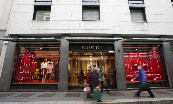 FILE - In this Thursday, Oct. 20, 2016 file photo, people walk in front of Gucci shop in Monte Napoleone street in Milan, Italy. Nigerian women who were trafficked to Italy to work as prostitutes have found new work in a handbag and dressmaking shop that recently received some fabulous raw materials: 4,000 meters (4,374 yards) of fabric leftovers from Gucci. The initiative was announced Wednesday, June 6, 2018 complete with a fashion show by the Nigerian dressmakers and a group of Italian design students who helped teach them to sketch and sew the designs, which mix Gucci silks, satins and cotton with bright African prints. (AP Photo/Antonio Calanni, file)