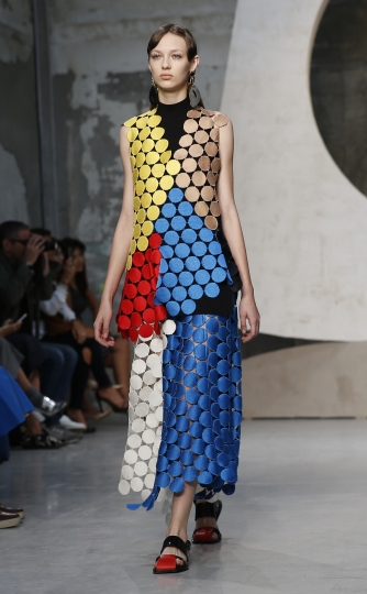 FILE - In this Sept. 27, 2015 file photo, a model wears a creation for Marni women's Spring-Summer 2016 collection, part of the Milan Fashion Week, unveiled in Milan, Italy, Sunday, Sept. 27, 2015. Casual luxury is driving global sales, forecast to grow 6 percent this year, as high-end consumers look for low-brow statements in T-shirts, sneakers and rubber sliders, according to a new study by consultancy Bain released Thursday, June 7, 2018. (AP Photo/Luca Bruno, file)