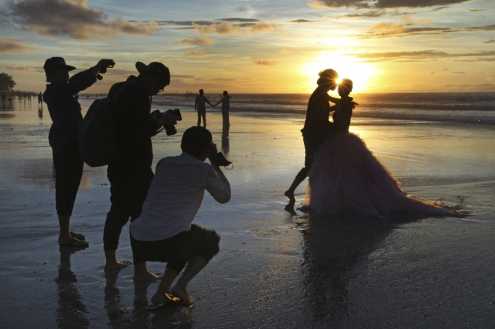 FILE- In this Jan. 18, 2017, file photo, photographers take photos of a tourist couple's wedding at the famous Kuta beach during sunset in Bali, Indonesia. According to a 2016 survey from wedding site The Knot, the average cost of an international destination wedding is $25,800. That figure may be within your event budget, but for guests, international airfare and multinight lodging could be out of reach. (AP Photo/Firdia Lisnawati, File)