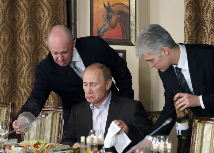 FILE - In this Friday, Nov. 11, 2011 file photo, businessman Yevgeny Prigozhin, left, serves food to then-Russian Prime Minister Vladimir Putin, center, during dinner at Prigozhin's restaurant outside Moscow, Russia. For many fans of food and football, a World Cup in Russia is unfamiliar territory. Russian cuisine has a reputation for being stodgy, unimaginative fare. While that may have been true for many in the days of Soviet supply shortages, a new generation of Russian in the World Cup's host cities mix together influences from across Europe and Asia. (AP Photo/Misha Japaridze, Pool, File)