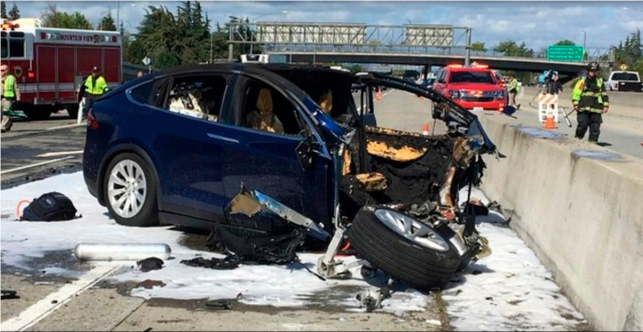 FILE - In this March 23, 2018, file photo provided by KTVU, emergency personnel work at the scene where a Tesla electric SUV crashed into a barrier on U.S. Highway 101 in Mountain View, Calif. Federal investigators say the Tesla using the company's semi-autonomous driving system accelerated just before crashing into a California freeway barrier, killing its driver. The National Transportation Safety Board issued a preliminary report on the crash on Thursday, June 7. (KTVU via AP, File)