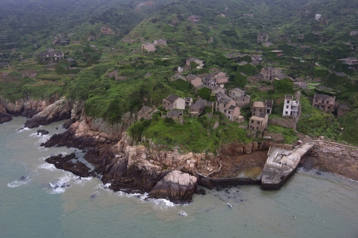 "This May 19, 2018, drone photo shows ruins of a building in the abandoned fishing village of Houtouwan on the remote island of Shengshan, 90 kilometers off the coast of Shanghai. Only 5 of the 3,000 residents remain in what some call a ""ghost village"" that draws visitors down perilous footpaths winding past structures worn down by roots, rain, vines and wind. (AP Photo/Sam McNeil)"