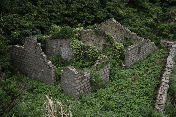 "This May 19, 2018, photo shows ruins of a building in the abandoned fishing village of Houtouwan on the remote island of Shengshan, 90 kilometers off the coast of Shanghai. Only 5 of the 3,000 residents remain in what some call a ""ghost village"" that draws visitors down perilous footpaths winding past structures worn down by roots, rain, vines and wind. (AP Photo/Sam McNeil)"