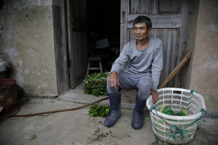 "In this May 19, 2018, photo, Lin Fazhen, 60, sits outside his home in the former fishing village of Houtouwan. He is one of the five residents left from the 3,000 that once lived in the village. The haunting beauty of the seaside village draws visitors down perilous footpaths winding past structures worn down by roots, rain, vines and wind on the remote island of Shengshan, 90 kilometers off the coast of Shanghai. Lin laughed when asked if the Houtouwan was haunted. ""I've lived in this world for such a long time, and have never met one, right?"" (AP Photo/Sam McNeil)"