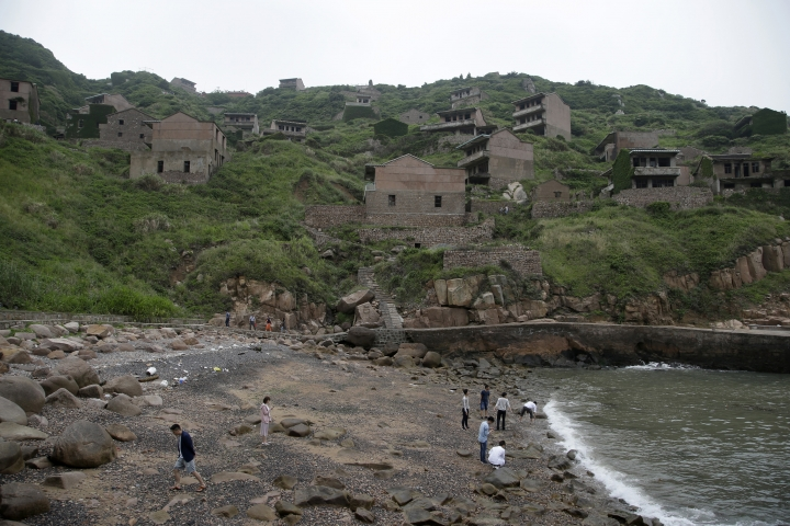 """In this May 19, 2018, photo, tourists play at the beach next to abandoned buildings in the former fishing village of Houtouwan on the remote island of Shengshan, 90 kilometers off the coast of Shanghai. Only 5 of the 3,000 residents remain in what some call a """"ghost village"""" that draws visitors down perilous footpaths winding past structures worn down by roots, rain, vines and wind. (AP Photo/Sam McNeil)"""