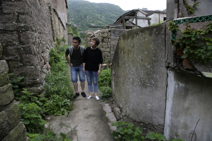 """In this May 19, 2018, photo, Zhu Mandi, 50, right, and her son, Wang Yi, 27, carefully walk through the former fishing village of Houtouwan to find the home their family abandoned in 1995. Only 5 of the 3,000 residents remain in what some call a """"ghost village"""" that draws visitors down perilous footpaths winding past structures worn down by roots, rain, vines and wind on the remote island of Shengshan, 90 kilometers off the coast of Shanghai. (AP Photo/Sam McNeil)"""
