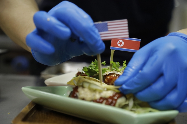 """FILE - In this June 7, 2018, file photo, miniature American and North Korean flags are used to decorate the """"El Gringo and El Hombre Cohete"""" tacos, inspired by the upcoming summit between U.S. President Donald Trump and North Korean Leader Kim Jong Un at the Lucha Loco restaurant in Singapore. Singapore is a city that takes great pride in its food, so it's not surprising that enterprising restaurateurs are using next week's historic summit between U.S. President Donald Trump and North Korean leader Kim Jong Un to showcase some culinary creativity. Restaurants are marking the city-state's time in the global spotlight with everything from red, white and blue cocktails to tacos named after the two leaders. (AP Photo/Wong Maye-E, FIle)"""