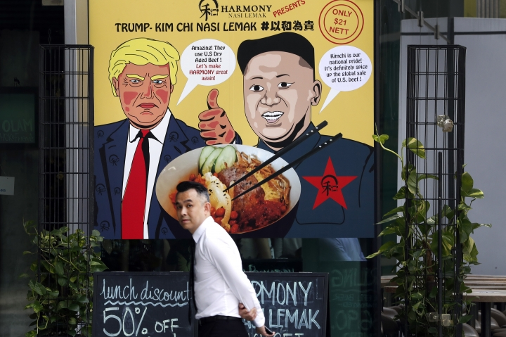 """FILE - In this June 7, 2018, photo, a man walks past an advertisement board of cartoon caricatures of U.S. President Donald Trump and North Korean leader Kim Jong Un which are supposed to be the inspiration behind a local dish, the """"Trump-Kim Chi Nasi Lemak"""" at a mall, in Singapore. Singapore is a city that takes great pride in its food, so it's not surprising that enterprising restaurateurs are using next week's historic summit between U.S. President Donald Trump and North Korean leader Kim Jong Un to showcase some culinary creativity. Restaurants are marking the city-state's time in the global spotlight with everything from red, white and blue cocktails to tacos named after the two leaders. (AP Photo/Wong Maye-E, File)"""