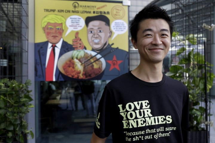 "In this June 7, 2018, photo, Zach Wen, 34, co-founder of Harmony Nasi Lemak poses in front of an advertisement board of cartoon caricatures of U.S. President Donald Trump and North Korean leader Kim Jong Un which are supposed to be the inspiration behind a local dish, the ""Trump-Kim Chi Nasi Lemak,"" in Singapore. Singapore is a city that takes great pride in its food, so it's not surprising that enterprising restaurateurs are using next week's historic summit between U.S. President Donald Trump and North Korean leader Kim Jong Un to showcase some culinary creativity. Restaurants are marking the city-state's time in the global spotlight with everything from red, white and blue cocktails to tacos named after the two leaders. (AP Photo/Wong Maye-E)"