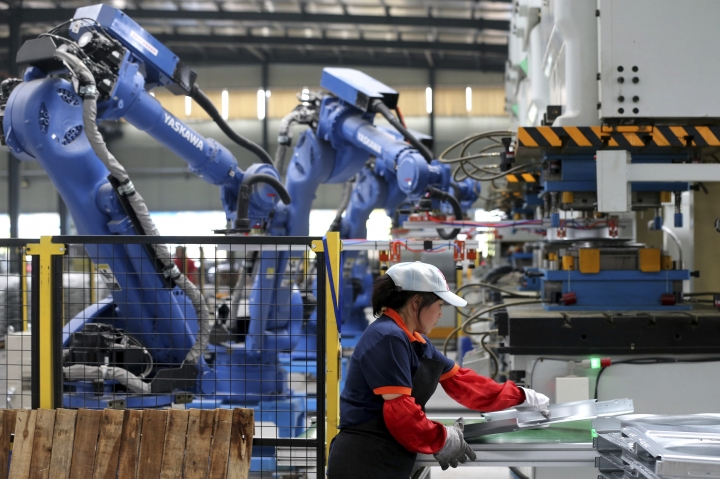 In this Tuesday, June 5, 2018 photo, a worker assembles air conditioner's components next to the robot arms at a factory in Suixi county in central China's Anhui province. China's politically sensitive trade surplus with the United States widened in May from a year earlier while its global trade gap shrank as imports accelerated. The latest reading on trade comes amid U.S. pressure on Beijing over its trade surplus and technology policy. (Chinatopix via AP)
