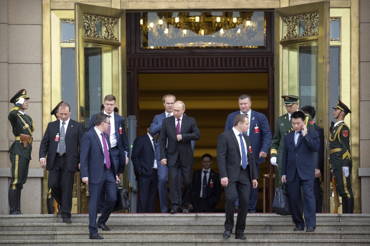 Russian President Vladimir Putin, center, leaves the Great Hall of the People after meeting with Chinese Premier Li Keqiang in Beijing, Friday, June 8, 2018. Putin is in China to attend the Shanghai Cooperation Organization (SCO) Summit in Qingdao. (AP Photo/Mark Schiefelbein)