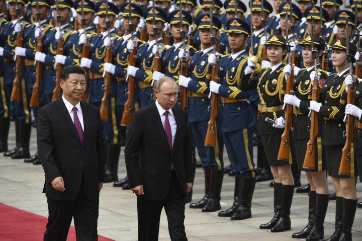 Russia's President Vladimir Putin, center, reviews a military honor guard with Chinese President Xi Jinping during a welcoming ceremony outside the Great Hall of the People in Beijing Friday, June 8, 2018. (Greg Baker/Pool Photo via AP)